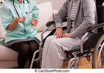Nurse talking with disabled patient at home