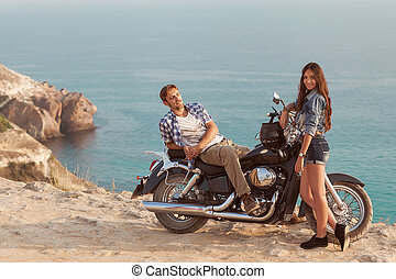 Biker man and girl in the sea