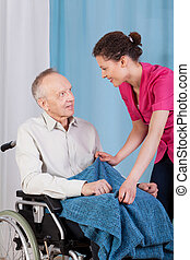 Nurse caring about disabled man - View of a nurse caring...