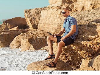 Fashionable young muscular guy resting on a rocky beach He...