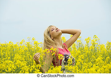 smiling at the sky - cute blond girl in yellow field smiling...