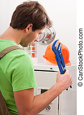 Broken central heating boiler and man with wrench