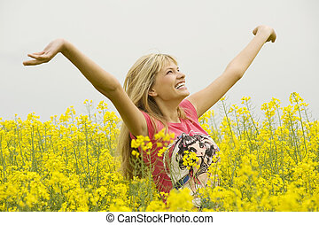 happy girl in yellow field - happy blond girl with open arms...