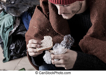 Poor man eating sandwich on the street