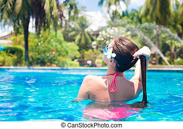 back view of long haired woman in pool