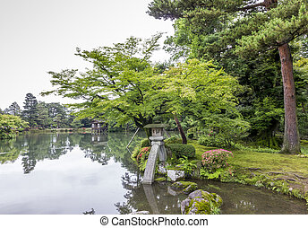 photo of a japanese garden with flowers, trees, lake, rocks...