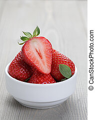 fresh ripe strawberryes in a simple white bowl, on wood...