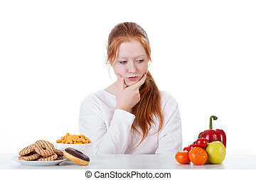 Wondering whether to eat sweets or vegetables - Teenage girl...