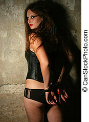 Arrested - Sexy lady with handcuffs by the wall