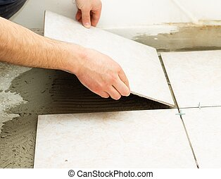 Ceramic Floor Tile Application - Manual worker covering...