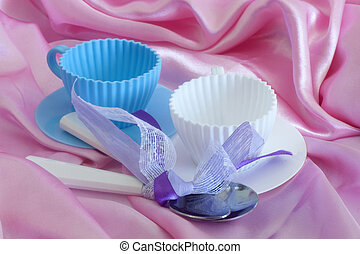 Elegant coffee cups and cutlery on fabric background
