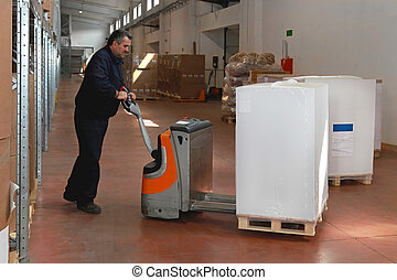 Warehouse worker - Maneuvering goods in warehouse with...