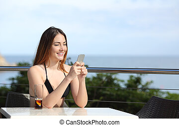 Happy woman using a smart phone in a terrace of a restaurant...