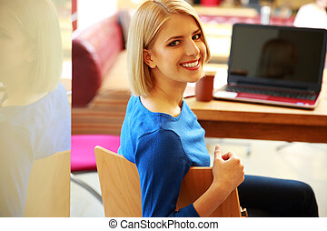Young happy woman sitting at the table with laptop and...