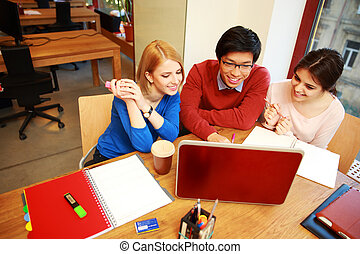 Young happy friends using laptop together