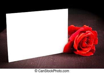 red rose and blank gift card for text on old wood...