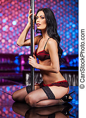 Sexy pole dancer looking at camera Sitting and holding pole...
