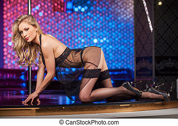 Sexy blond pole dancer seductively posing on camera. Erotic...