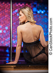 Back view of sexy blond striptease dancer. Sitting on stage...
