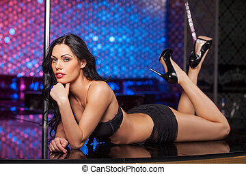 Sexy brunet dancer laying on the stage. Fashion posing in strip club