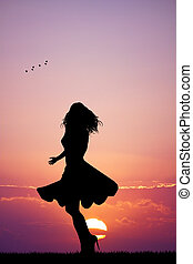 Woman with skirt blowing in the wind at sunset