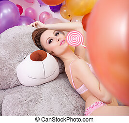 Image of beddable woman posing with lollipop