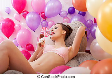 Image of sexy young woman licks lollipop - Studio shot of...