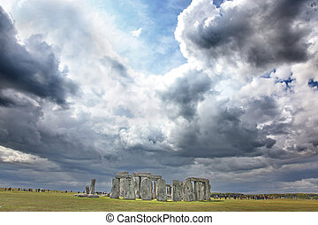 Stonehenge historic site on green grass under dramatic sky....