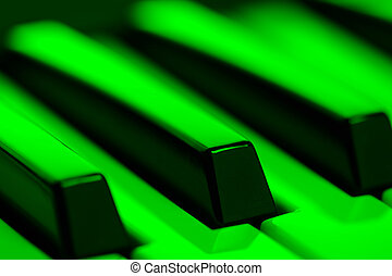 Piano Keys in Green Light - A close-up of piano keys in...