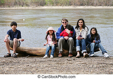 Father with his children on fallen log - Father sitting with...