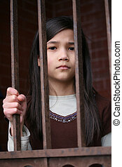 Unhappy girl standing behind bars of prison or gate