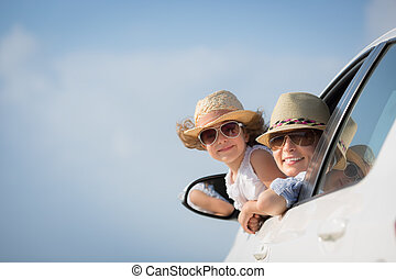 Happy woman and child in car against blue sky background....