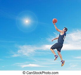 lay up in the sun - basketball player doing a lay up in the...