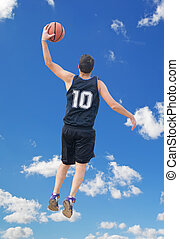 left dunk in the sky - basketball player dunking with the...
