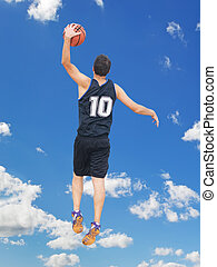 left hand dunk in the sky - basketball player dunking with...