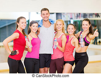group of happy people in gym with water bottles - fitness,...