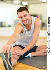 smiling man stretching on mat in the gym