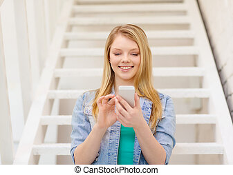 smiling female student with smartphone - education and...