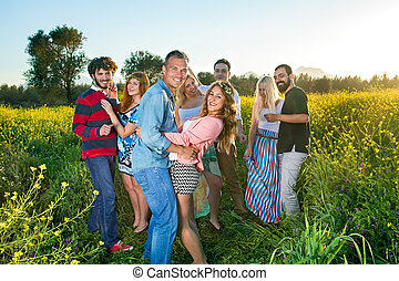 Four happy young couples having a party in the countryside...