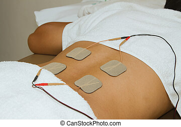Patient applying electrical stimulation therapy TENS on his...