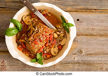Sliced savory meatloaf with mushrooms and vegetables served...