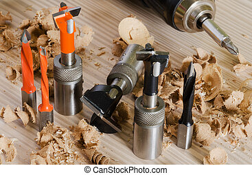 Machine tool cutters and drill bits in the sawdust on wood...