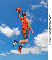 orange dunk in the sky - basketball player dunking with the...