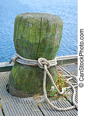 old wooden mooring bollard with rope in the ship port