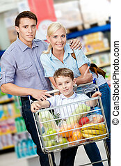 Family drives cart with food and boy sitting there - Family...