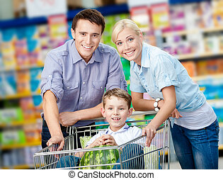 Family drives shopping trolley with food and son who sits...