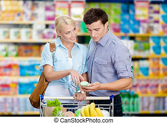 Young couple discussing the shopping list and chosen products
