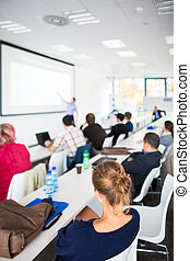 People listening to a presentation in a modern, bright...