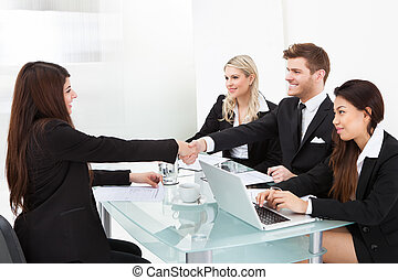 Colleagues Shaking Hands At Desk - Business colleagues...