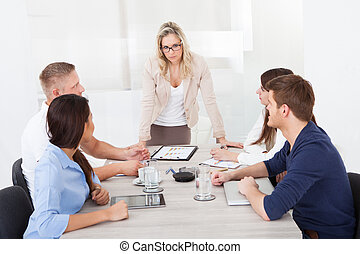 Angry Businesswoman Standing At Desk In Meeting - Angry...